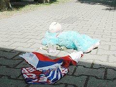 Devatenáctiletý mladík ubodal o dva roky staršího známého v úterý na hřbitově v Doksech. Kriminalisté útočníka obvinili z vraždy. Na hřbitov blízcí donesli plyšáka a národní šálu.