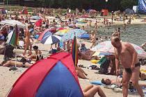 Hlava na hlavě. Takový obrázek se na plážích kolem Máchova jezera během letošní sezony zatím nenaskytl.