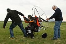 Miroslav Oros má za sebou přes tisíc šest set kilometrů na paraglidu. Start na letišti Ramš. Správce letiště pomáhá Miroslavu Orosovi zvednout se s krosnou.
