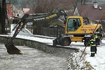 Lopatka bagru se na Svitávce v Zákupech noří mezi ledové kry. Tisíce kusů ledu se potokem prodírá do Ploučnice.