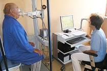 Pacient  usazený ve vyšetřovací kabině bodypletysmografu provádí různé dechové manévry podle pokynů zdravotní sestry.