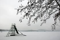 Ledová poklička pokryla v těchto dnech Máchovo jezero. První bruslaři ale musí ještě několik dní počkat, než led pořádně zesílí. Zatím se hodně prolamuje, nejvíc u břehů. O část z nich se teď svádí bitva.
