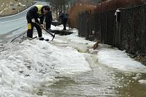 Odsekat led, aby voda z polí nad rodinnými domy v Kravařích měla kudy odtékat, museli jak místní, tak i hasiči.