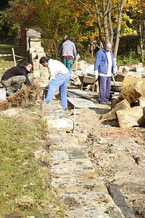Zeď se staví na novém betonovém základě. Dělníci ke stavbě používají původní kameny, aby nová zeď vypadala stejně jako před svým zborcením.