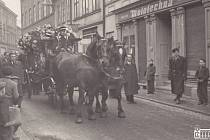 Pohřeb Jana Kupce. Pohřební kočár tažený koňmi před domem Jana Kupce v Sokolské ulici. Za kočárem šla dlouhá řada myslivců profesionálních i členů spolků.