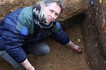 Archeolog Petr Jenč vyzvedává historický střep z míst, kam dlouhá staletí slunce nesvítilo.