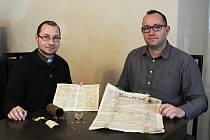 Farář Kamil Škoda (vlevo) a starosta Bezdězu Jaroslav Cinkl drží obsah časové schránky z roku 1868.Vybledlá fotografie s odloupnutými zády, tři křížky, úhledně napsaný dopis a lehce poškozené noviny.