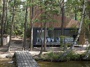 Náhrada starší chaty na břehu jezera v borovicovém lese respektuje unikátní přírodní charakter místa a kopíruje zastavěnou stopu původního objektu.