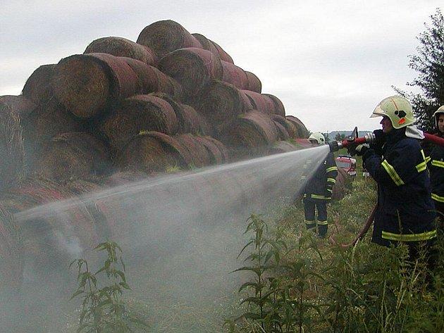 Hasiči prolévají vodou hořící balíky slámy.