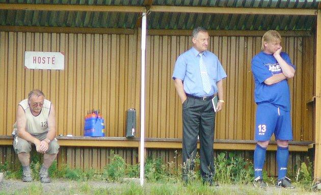 Osamocený na ní zůstal trenér Jiří Jelínek (v dresu). Vedle něj stojí delegát utkání Karel Fischer, který se zde ukryl před lijákem.