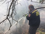 Požár lesního porostu v těžkém terénu ve svahu u obce Dubá - Korce.