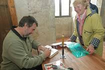Spisovatel Vlastimil Vondruška podepisuje svou novou knihu.