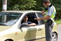 Policejní hlídka kontroluje projíždějíci