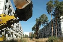 """Vydlabaná cesta mezi """"domy duchů"""", rozpadajícími se bytovkami po sovětské armádě. Objekty patří firmě Vladimíra Grössera, ale pozemek mezi nimi je města Ralsko."""