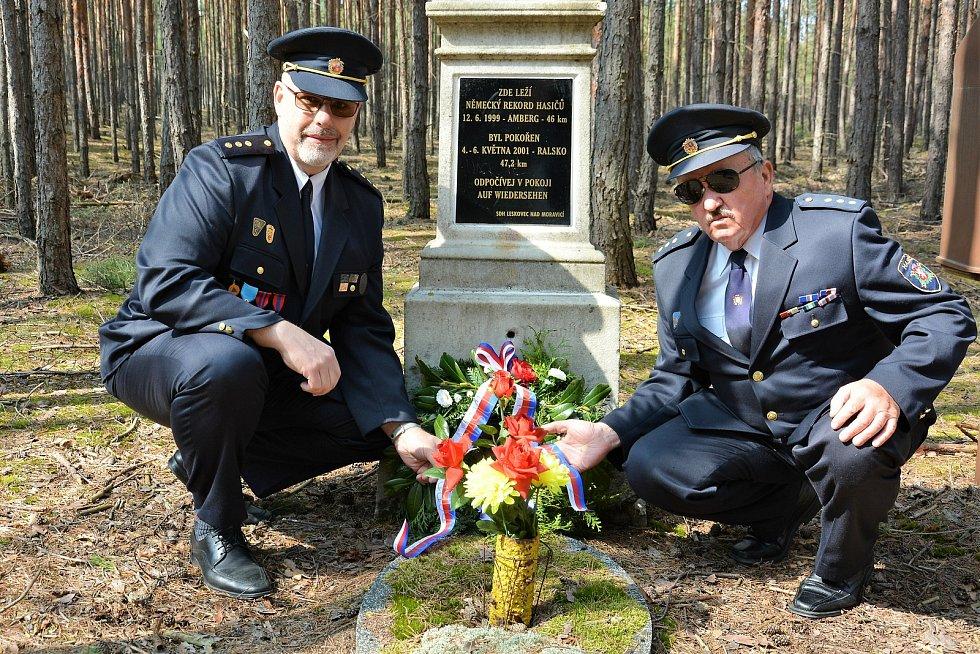 Jiří Sucharda a Jiří Havner jdou s věncem k pomníčku připomínajícím rekord z roku 2001, na silnici za Borným.