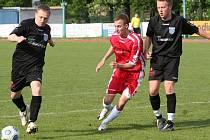 Dražovický fotbalista mezi dvěma slavkovskými (na snímku) protivníky, takový pohled na podzim fanoušci fotbalu na Vyškovsku neuvidí. Mužstva sice zůstala v I.A třídě, budou ale hrát odlišné skupiny.