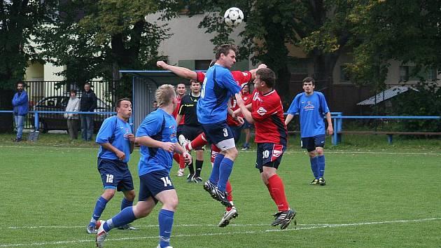 Hlavičkuje hrající trenér Šaratic (v modrém) Michal Odehnal.