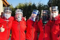 Pracovníci charity s ochrannými štíty.