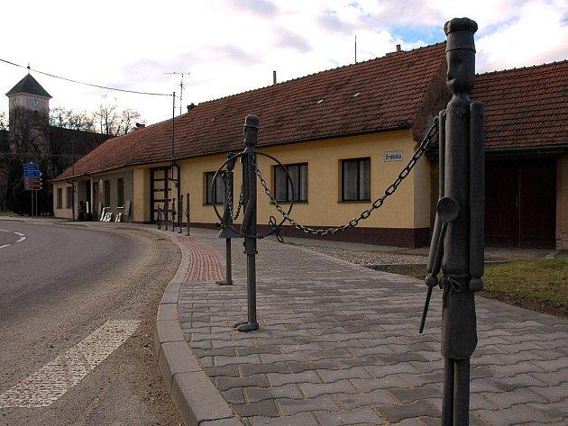 Netradiční zábradlí v Křenovicích, jehož sloupky znázorňují tradiční řemesla a povolání. Autorem je křenovický umělecký kovář Oldřich Bartošek.