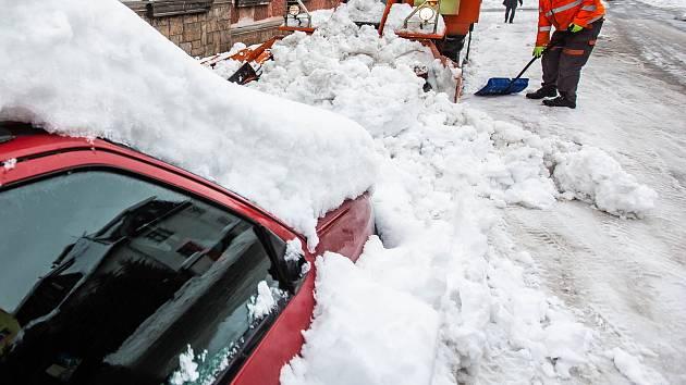 Parkování aut na zasněžených ulicích.