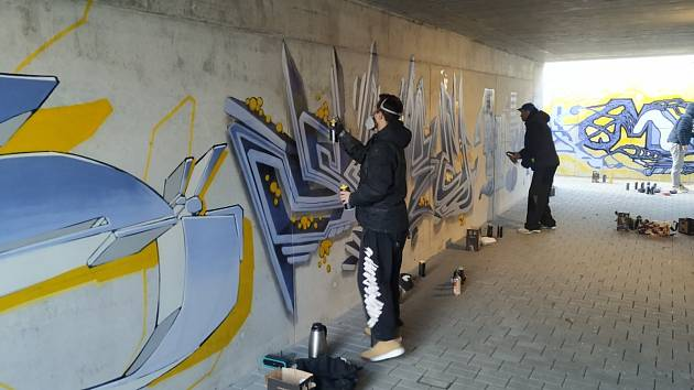 Autoři graffiti při práci.