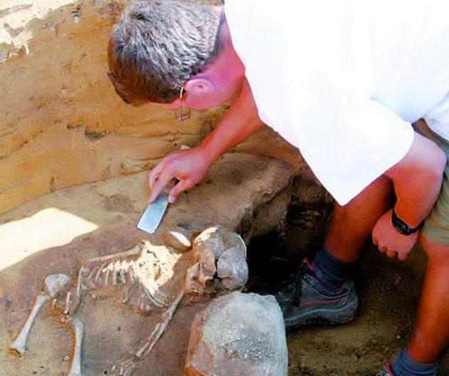 Antropolog Jiří Kala z brněnského Ústavu archeologické památkové péče očišťuje kostru dítěte v sídlištní jámě velatické kultury, kterou v pátek archeologové objevili ve Vyškově.