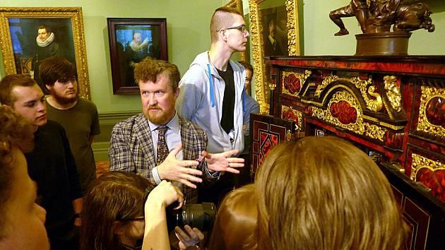 Restaurátor a historik umění Ryšánek vysvětluje studentům, jak opravit nábytek.