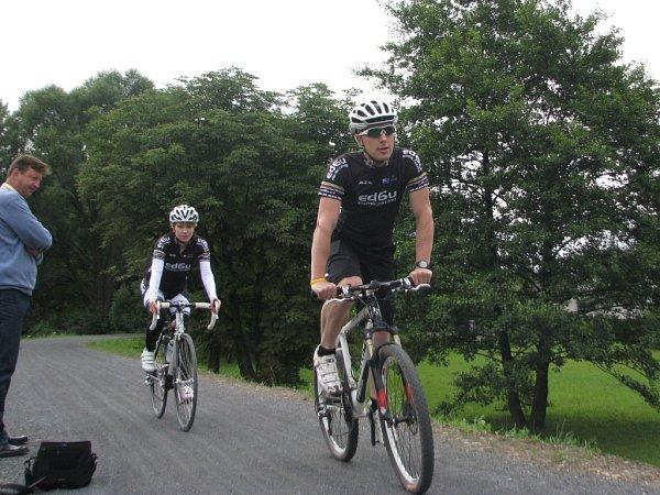 Po povrchu cyklostezky tvořené zaválcovaným štěrkem se prohánějí cyklisté na různých typech kol.