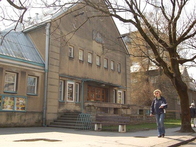 Žena prochází kolem budovy frýdlantského kina. Podobný pohled se už brzy stane historií, město nyní starý dům prodává k demolici developerské firmě.