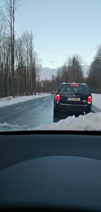 Kolona automobilů na zledovatělé silnici.