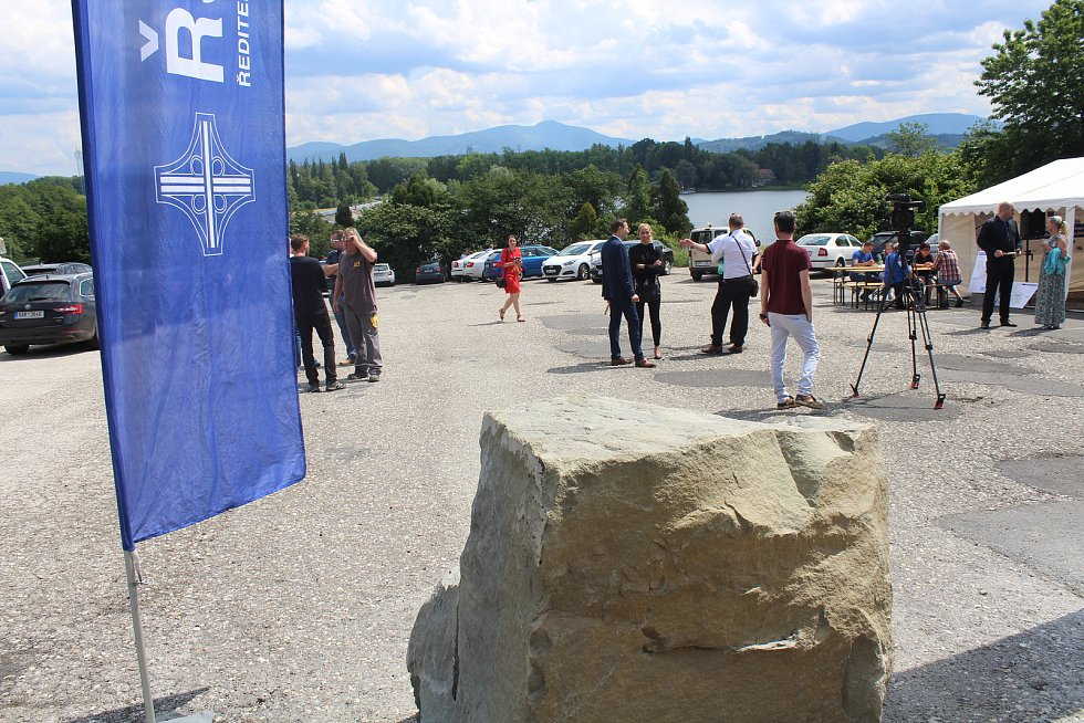 V popředí základní kámen a v pozadí přehrada Olešná a také Beskydy.