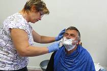 Dobrovolnice se právě pustila do holení Pavla Hofjírka, který spokojeně seděl.