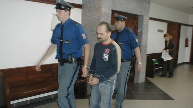 Eskorta odvádí Tomáše Danela ze soudního jednání. Muž byl již propuštěn na svobodu.