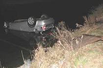 Vůz po smyku prorazil zábradlí a skončil na střeše v řece Ostravici. Řidič je po operaci udržován v umělém spánku.
