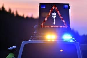 Nebezpečí na silnici - Rozsvicený výstražný trojúhelník na střeše policejního auta. Ilustrační foto.