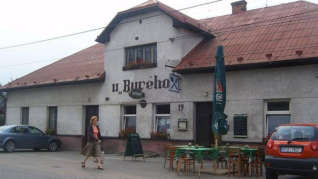 Žena prochází kolem restaurace U Burého v Hrádku.