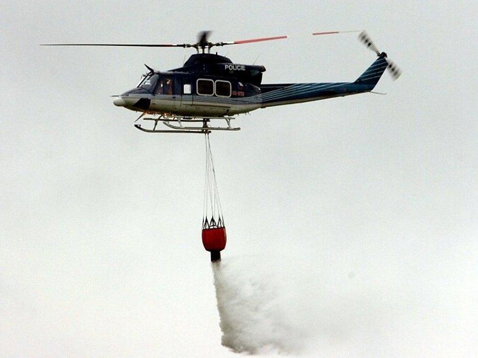 Policejní vrtulník s bambi vakem pro hašení požárů ve spolupráci s hasiči.