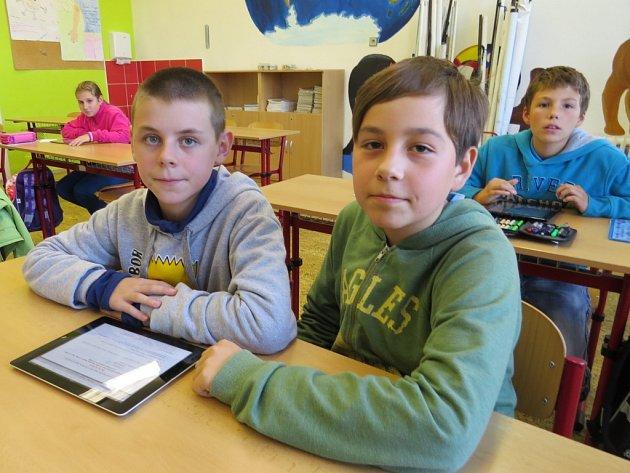Žáci ve škole pracují s tablety.