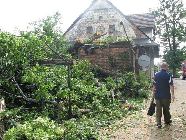 Muž prochází kolem zničené garáže v Sedlištích, na kterou spadl během bouřky vzrostlý strom. Udeřil do něj blesk.