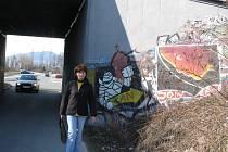 Žena jde kolem graffiti na místeckém podjezdu, který patří Ředitelství silnic a dálnic.