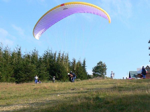 Na snímku tandem. Piloti při něm nabízejí let na dvoumístném paraglidu těm, kteří si sami do vzduchu netroufají.
