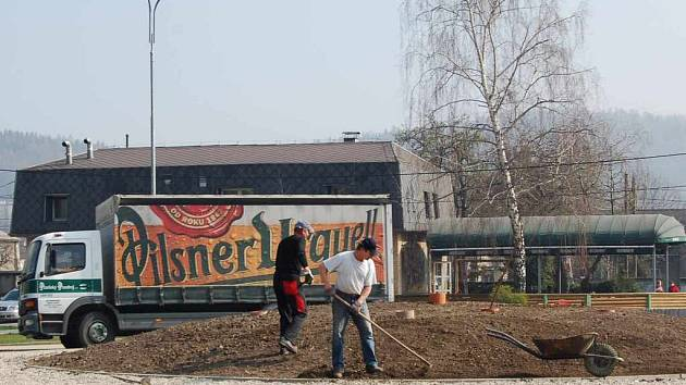 Dělníci upravují pozemek, na němž bude plastika Kytice stát.