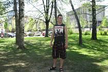 Tomáš Vrána stojí v místech, kde chce investor vybudovat polyfunkční dům. Mladý muž žije v sousedním patnáctipatrovém paneláku a říká, že záměr se mu nelíbí.