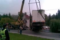 Kamion s návěsem vyprošťují jeřábem na vozovku. Nehoda se obešla bez zranění. Vyžádala si však námahu záchranářů a přechodné omezení dopravy.