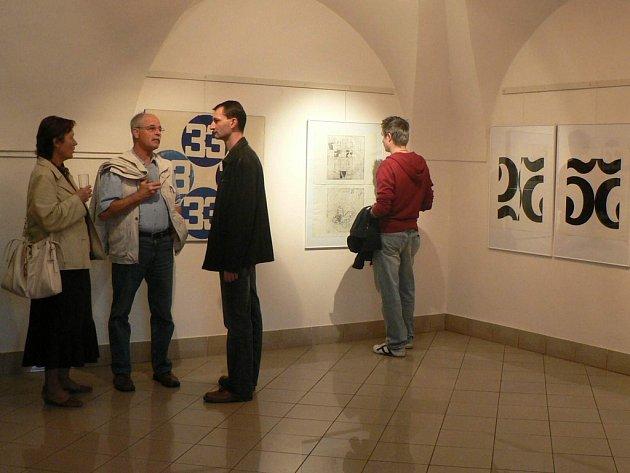 Příznivci Miloše Urbáska diskutují nad jeho dílem během vernisáže.