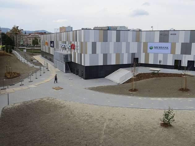 Listopad 2014.Úpravou prochází také okolí nákupního centra, vpodzemním podlaží objektu vzniklo velkokapacitní parkoviště.