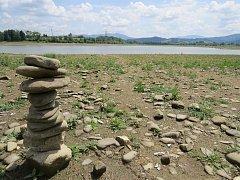 Rostoucí tráva dokazuje, že dno přehrady je už řadu měsíců odkryté. Povalující se kameny lákají ke stavbě mohyl.