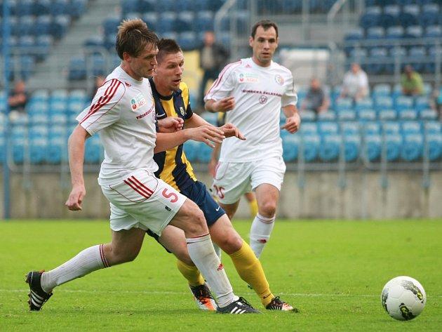 Třinecký obránce Radek Kuděla (v bílém) bojuje o míč s Tomasem Radzenivičiusem.