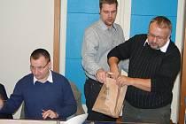 Vedoucí odboru vnitřních věcí magistrátu Radovan Horák (na snímku uprostřed) nabízí losy na umístění trojnožek zástupcům politických stran.