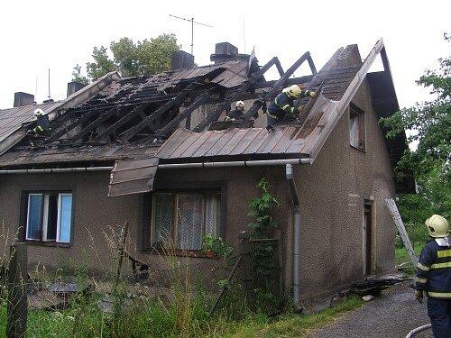 Při požáru domu v Třinci se hasiči museli prodírat ohořelými trámy na střeše.